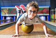 Kid laying on top of bowling ball